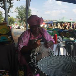 Woman weaving a basket on Kendra's African incentive Trip