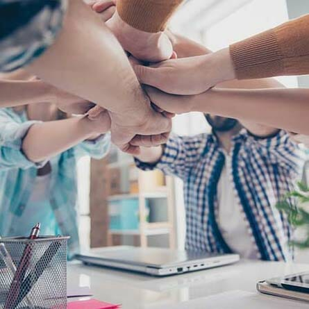 Employee team with hands together indicating trust